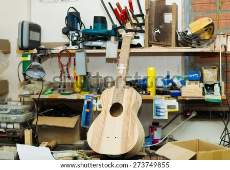Unfinished acoustic guitar and workshop equipment   - stock photo