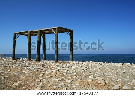 Unfinished and abandoned construction of a summerhouse on the beach with the sea and cloudless sky in the background - stock photo