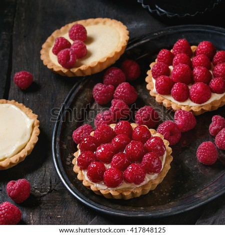 Unfinished and ready to eat tartlets with custard and fresh ripe raspberries, served on vintage metal tray with baking forms and textile napkin over old wooden table. Dark rustic style. Square image - stock photo