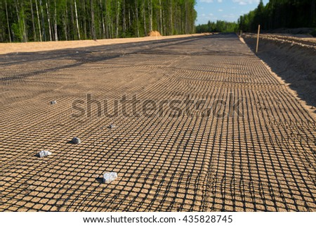 Unfinished asphalt country road in pine forest. Net on sand. Under construction - stock photo
