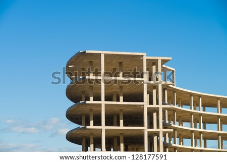 Unfinished building structure against blue sky - stock photo