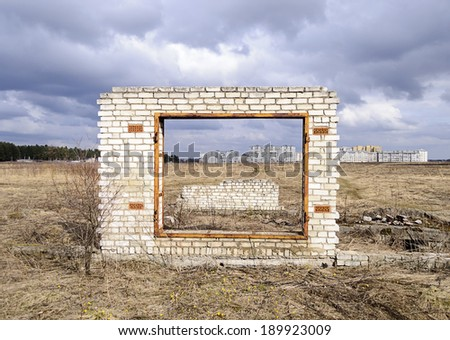 Unfinished garage gate on city outskirts background, cloudy spring day - stock photo