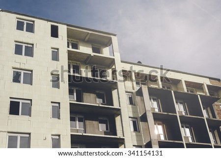 Unfinished generic residential building, construction site with no workers, project not completed, retro toned - stock photo