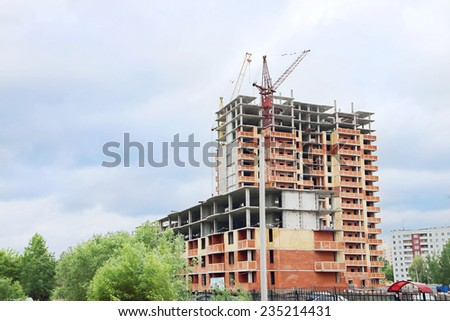 Unfinished high-rise apartment building with brick walls and crane at summer - stock photo