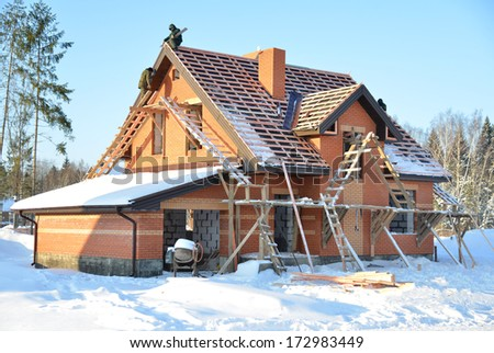 Unfinished house of brick site under construction with wooden roof - stock photo