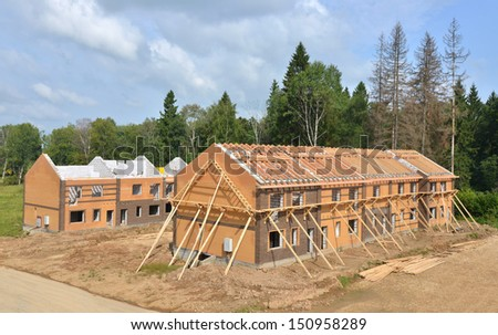 Unfinished houses of brick site under construction with wooden roof - stock photo