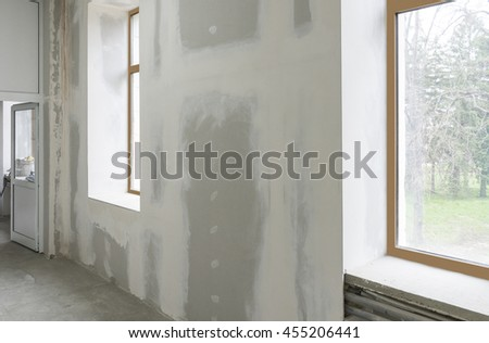 Unfinished interior of apartment  under construction with window - stock photo