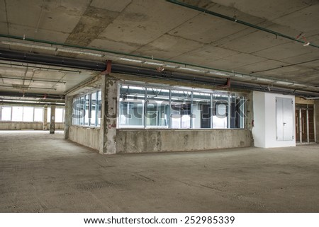 Unfinished interior of business center under construction in grey colours. Lift shaft - stock photo