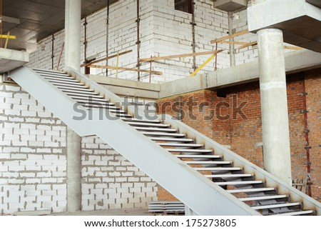 Unfinished interior space with iron staircase and brick walls