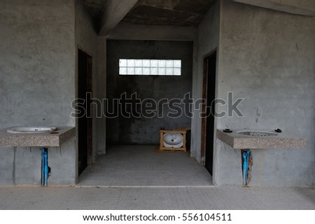 Unfinished public toilet, two water dispensers