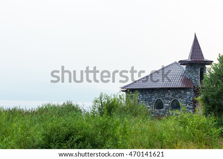 unfinished small castle of stone on a lake shore Ural, Russia