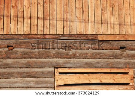 unfinished wooden village house with boarded up window. - stock photo