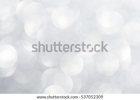 Unfocused abstract silver white glitter bokeh holiday background. Winter xmas holidays. Christmas.