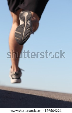 Unfocused man legs running on the asphalt with the sky in the background - stock photo
