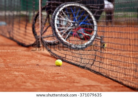 Unfocused wheelchair tennis player seen behind a tennis net on a clay court - stock photo