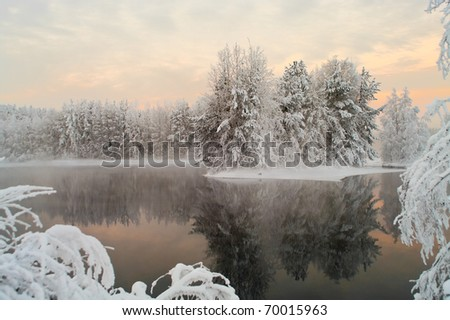 Unfrozen lake in the winter forests of Karelia, Russia. Black water and snowy brunches - stock photo