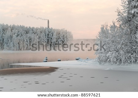 Unfrozen lake in the winter forests. Wastewater from sewage water plant. Black water and snowy brunches. Smoke chimney - stock photo
