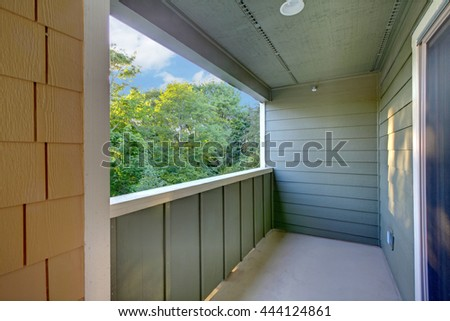 Unfurnished covered balcony with blue walls, white trim and a view. - stock photo