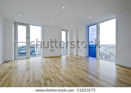 unfurnished dual aspect living room with laminate floor - stock photo