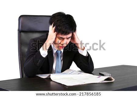 Unhappay Asian young businessman sitting with serious problem at office desk (with clipping path )