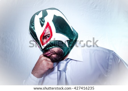 Unhappy, angry businessman with Mexican wrestler mask, expressions of anger and rage - stock photo