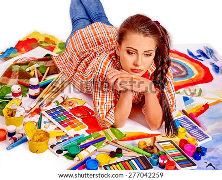 Unhappy artist woman lying on paint palette. Creative crisis. - stock photo