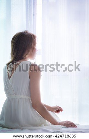 Unhappy Asian woman sitting on the bed, conceptual of waiting, love,sadness and broken heart. - stock photo