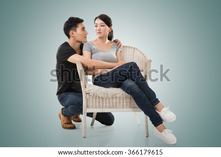 unhappy Asian young couple sit on sofa