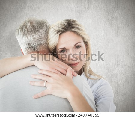 Unhappy blonde hugging her husband against weathered surface - stock photo