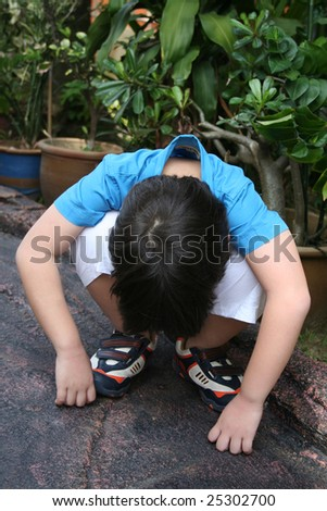 Unhappy boy in blue shirt squatting in the park - stock photo