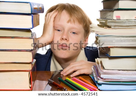 unhappy boy sitting by the desk full of books - stock photo