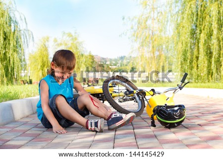 Unhappy boy suffering from injured knee pain - stock photo
