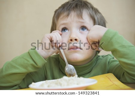 Unhappy boy with food looking up while sitting at table - stock photo