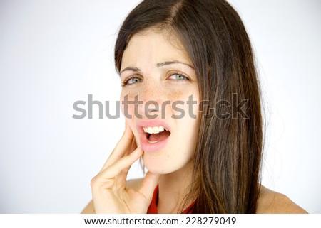 Unhappy brunette needing to go to a dentist - stock photo