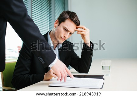 Unhappy business man listen to his boss - stock photo