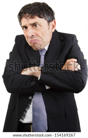 Unhappy businessman standing with his arms folded grimacing , isolated on white