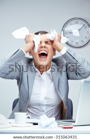 Unhappy businesswoman crying at workplace - stock photo