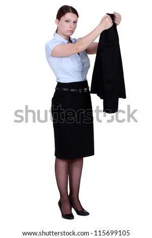 Unhappy businesswoman hanging her blazer up - stock photo