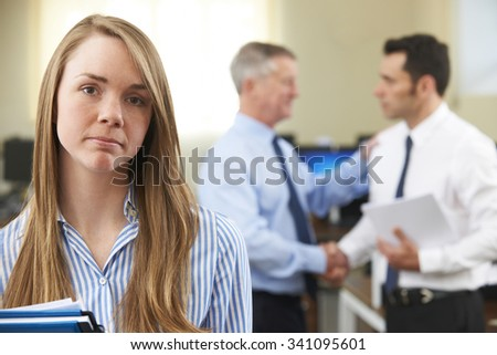 Unhappy Businesswoman With Male Colleague Being Congratulated - stock photo
