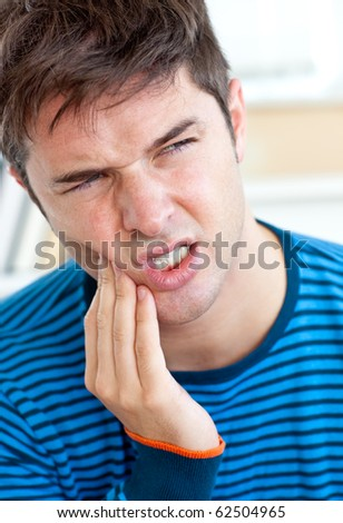 Unhappy caucasian man having a toothache in the living-room at home - stock photo