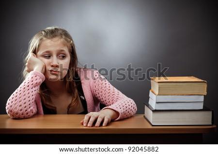 Unhappy caucasian schoolgirl at her desk, near a stack of books - stock photo