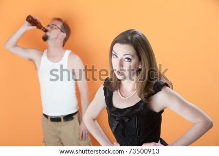 Unhappy Caucasian wife with alcoholic husband on orange background - stock photo