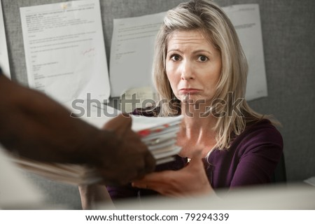 Unhappy Caucasian worker given a stack of files at a cubicle - stock photo