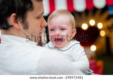 Unhappy child in the hands of daddy. Image of young dad with cute little daughter in his arms. Father and baby girl child in cafe. - stock photo