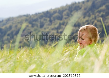Unhappy child is sitting in the grass - stock photo