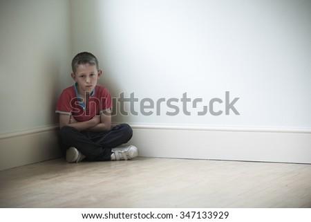 Unhappy Child Sitting In Corner Of Room - stock photo