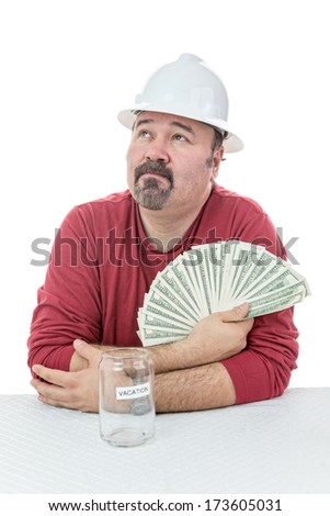 Unhappy construction worker holding-on to tax money and dreaming with what else he could do with it - stock photo