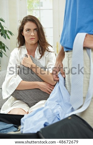 Unhappy couple breaking,  sad woman sitting on on couch hugging pillow.