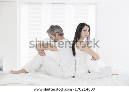 Unhappy couple ignoring each other sitting back to back on bed during a conflict - stock photo