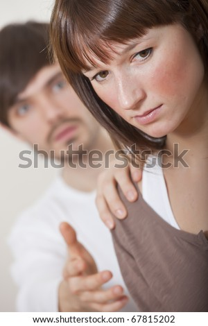 unhappy couple - man holding woman on her shoulder - stock photo